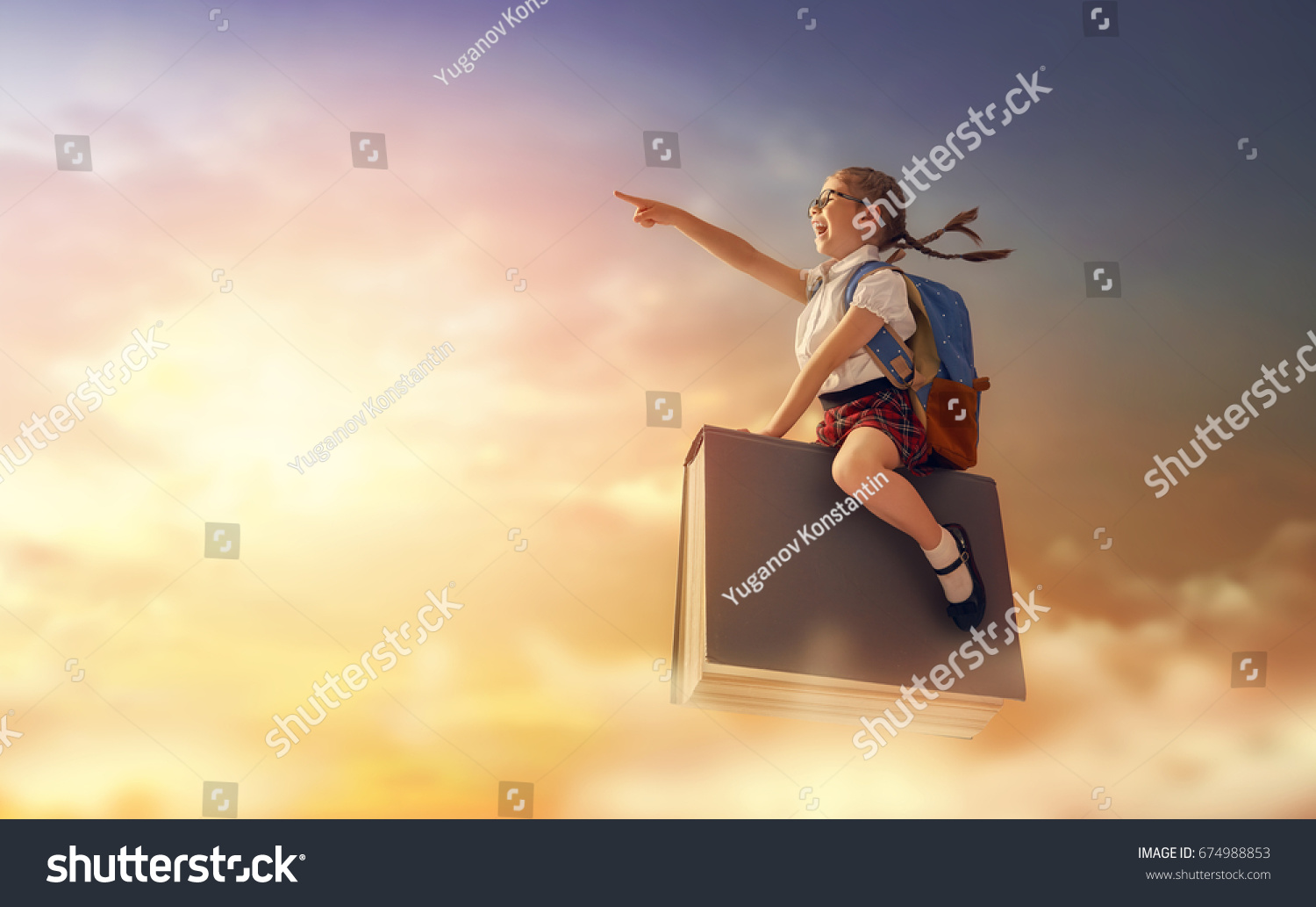 Back to school! Happy cute industrious child flying on the book on background of sunset sky. Concept of education and reading. The development of the imagination. #674988853