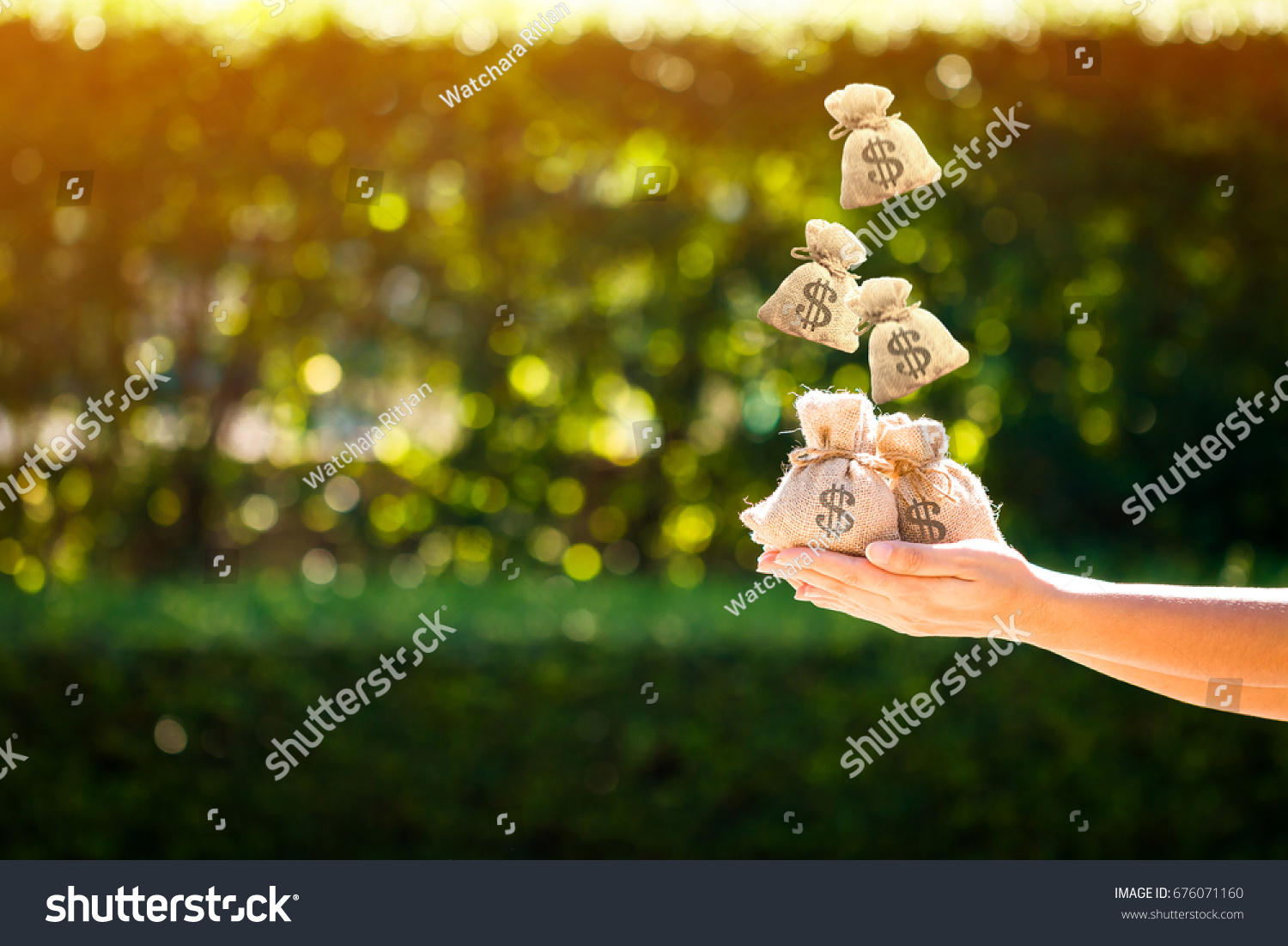 Women hands hold a money bags and dropping on the top in the public park for loans to planned investment in the future concept. #676071160