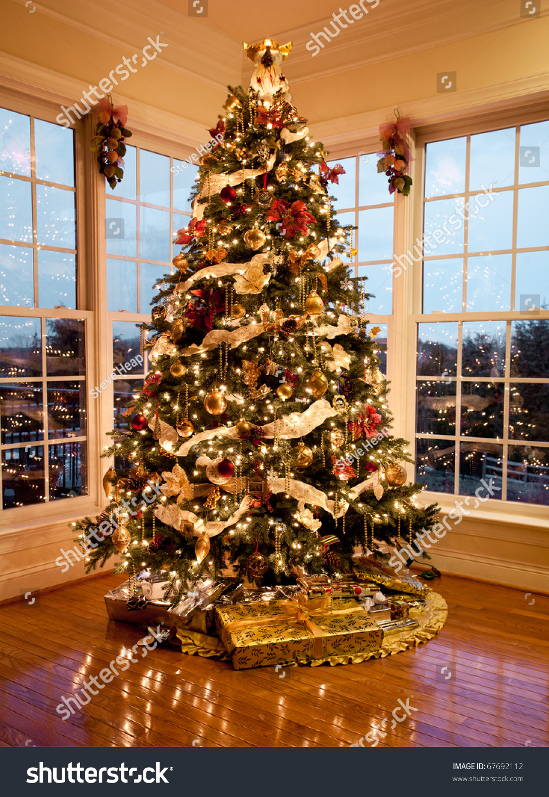 Christmas tree with presents and lights - Christmas Tree With Presents And Lights Reflecting In Windows Around The Tree In Modern Home