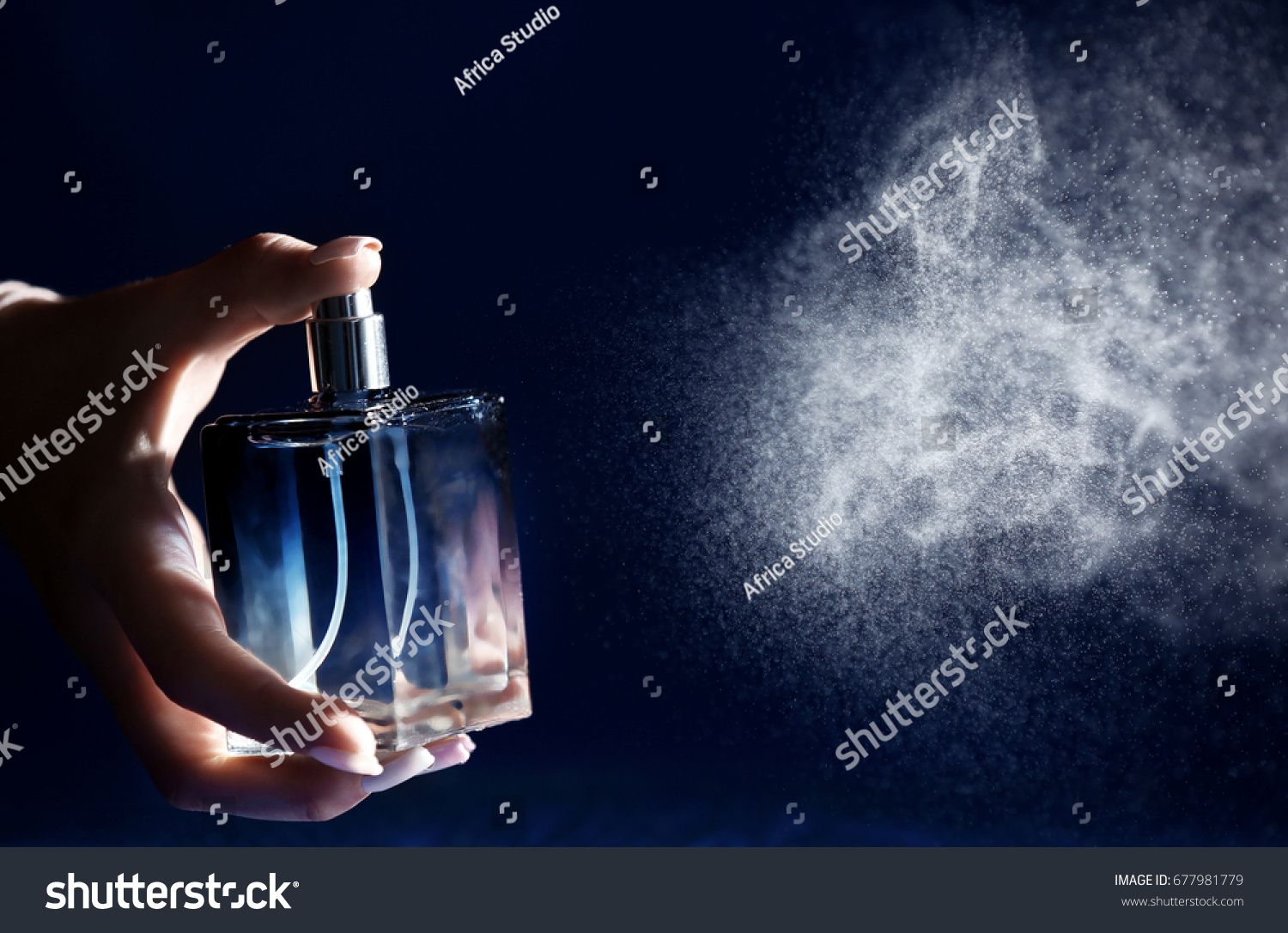 Woman spraying perfume on dark background, closeup