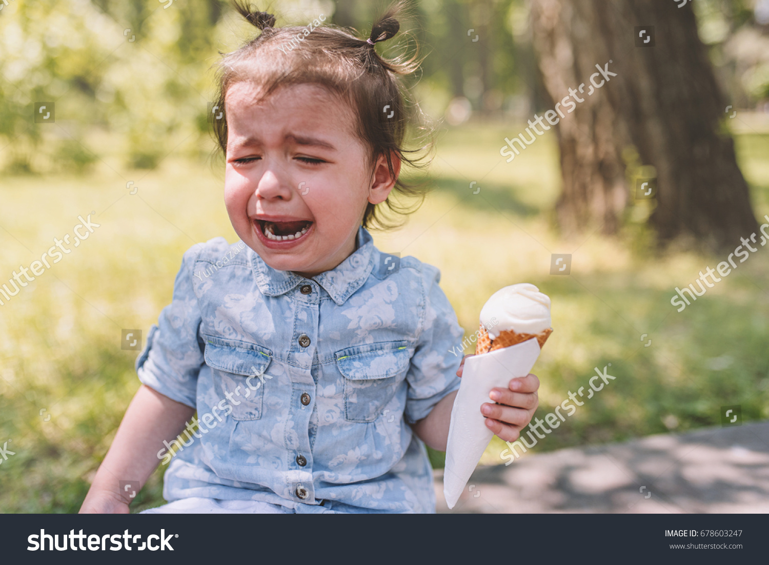 a33906d5bf20 Portrait of sad crying child with ice-cream cone in hand in the park.