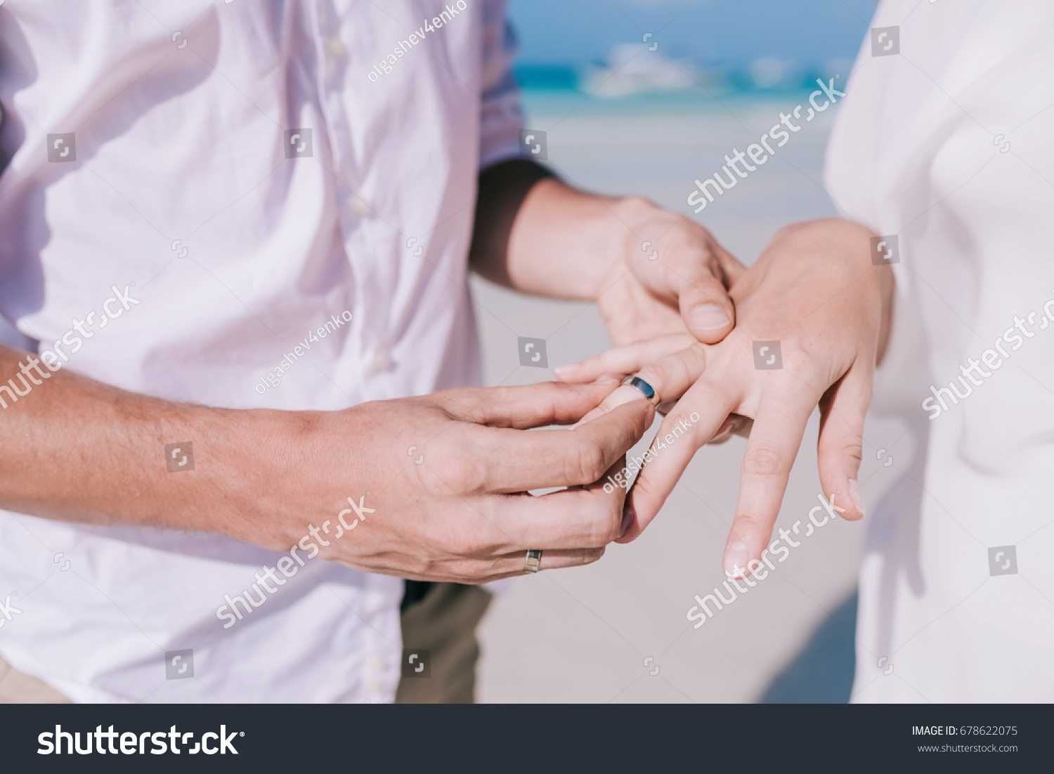 Bride and groom change rings at their wedding on the white sand ...