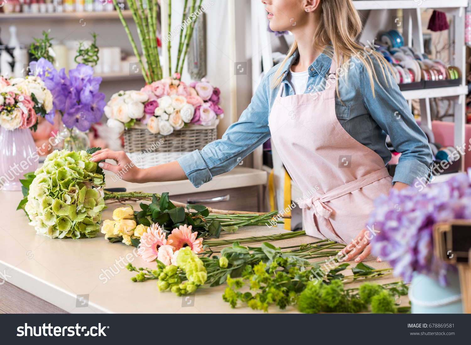 Cropped shot young blonde florist apron stock photo edit now cropped shot of young blonde florist in apron arranging beautiful flowers in flower shop izmirmasajfo