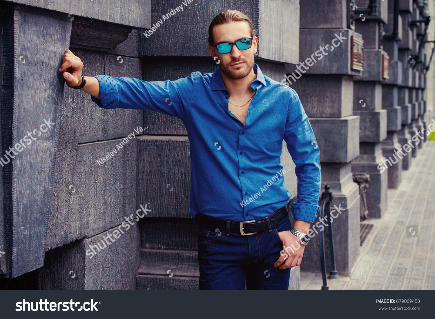 46d0a0a1 Handsome young man in jeans clothes stands on a city street. Men's fashion.