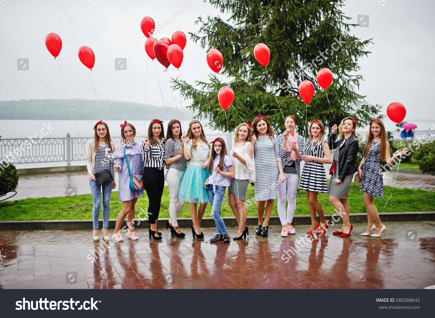 Eleven amazingly-looking braidsmaids with stunning bride posing with red heart-shaped balloons on the pavement against the lake in the background. #680308642