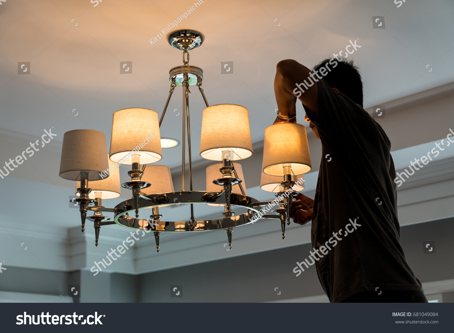 Electrician change light bulb chandelier on stock photo royalty electrician change the light bulb of chandelier on the ceiling arubaitofo Images