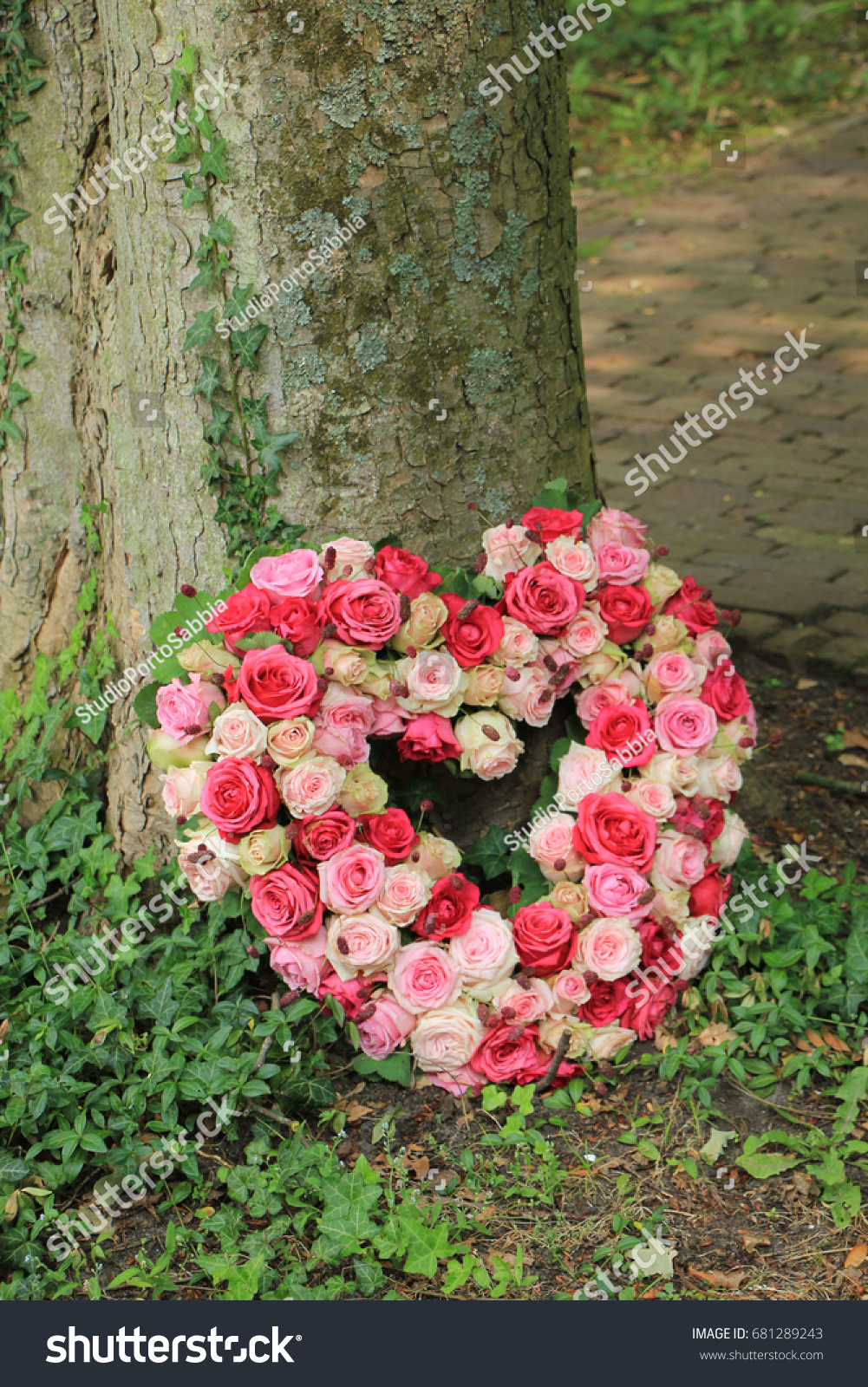 Heart shaped sympathy flowers funeral flowers stock photo edit now heart shaped sympathy flowers or funeral flowers near a tree izmirmasajfo