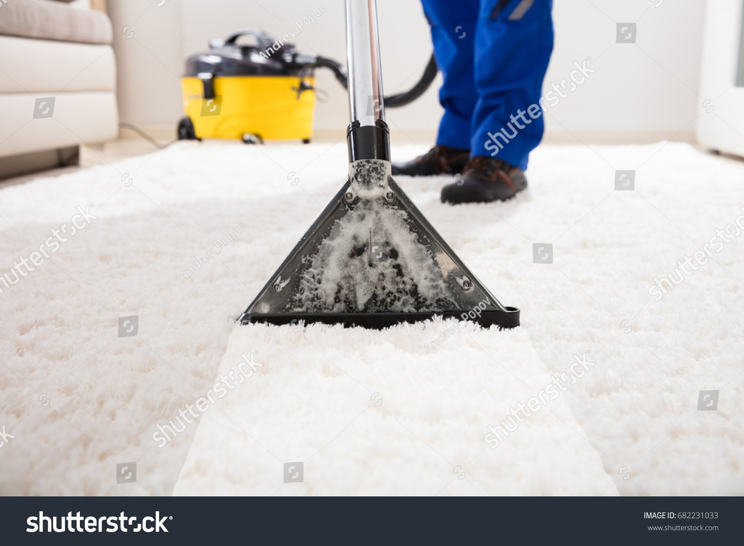Close-up Of A Janitor Cleaning Carpet With Vacuum Cleaner At Home #682231033