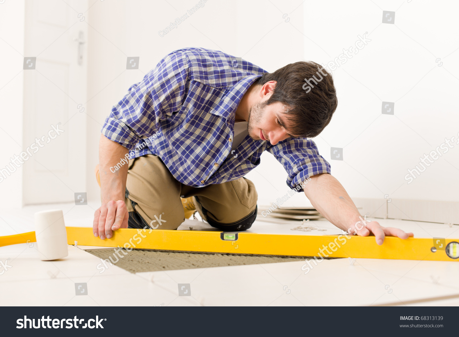 Home tile improvement handyman level laying stock photo royalty home tile improvement handyman with level laying down tile floor dailygadgetfo Choice Image