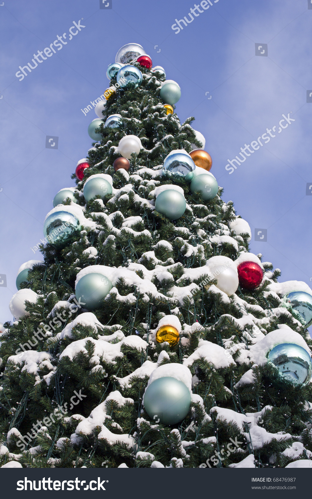 Large Outdoor Christmas Tree Decorated With Balls And Covered With Snow