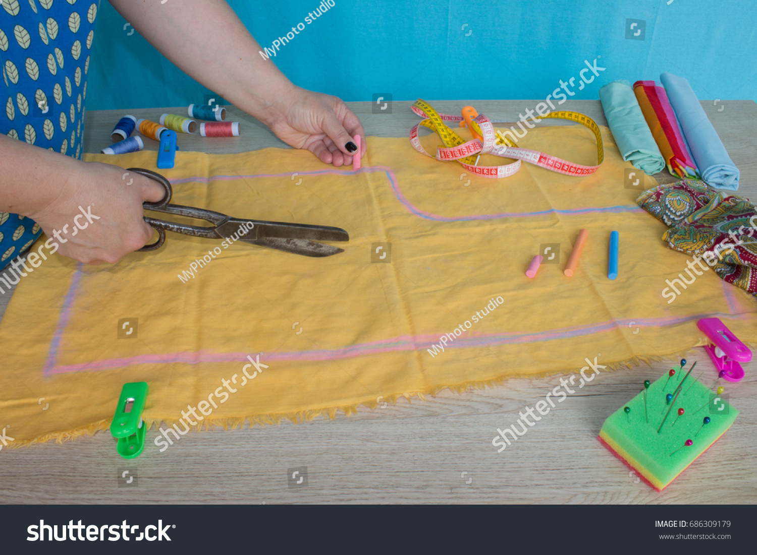 woman hands sewing yellow cloth outdoors. Tailor hands working with scissor and suit textile cloth #686309179