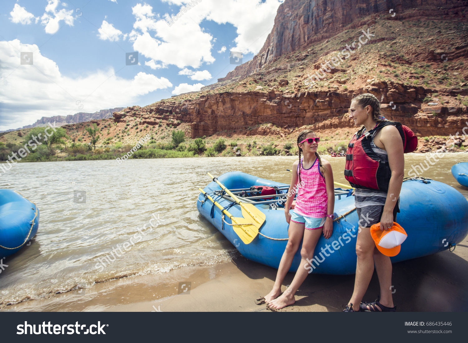 Smiling Child And Adult Women Ready To Board A Large Inflatable Raft As  They Travel Down