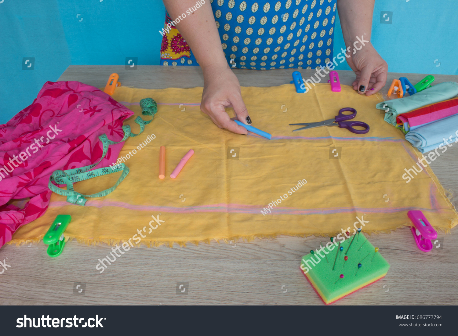 closeup of woman hands sewing yellow cloth outdoors. Woman's Hand Sewing Quilt #686777794