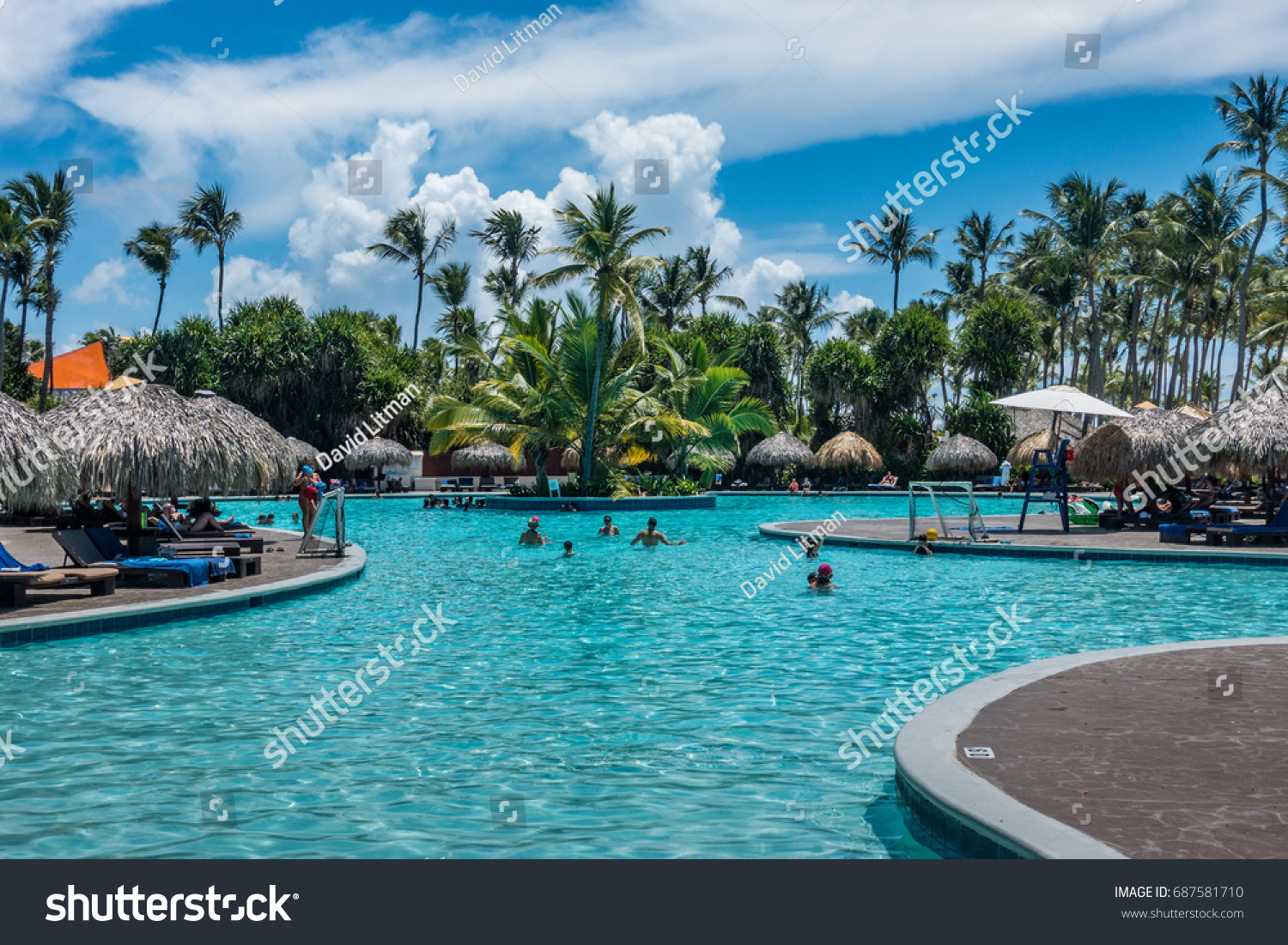 Punta Cana, Dominican Republic - July 26, 2017: People enjoy the pool area at a vacation resort (Club Med)on a partly cloudy summer day along the Caribbean Sea.
