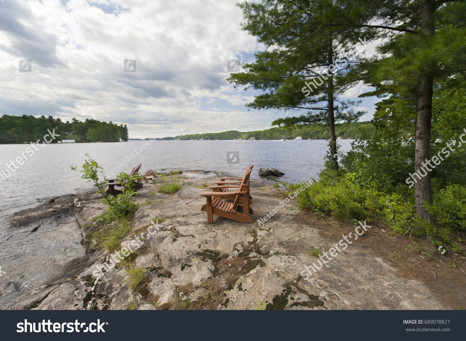 Muskoka Chairs On A Rock Formation Facing A Calm Lake. Across The Lake  Thereu0027s A