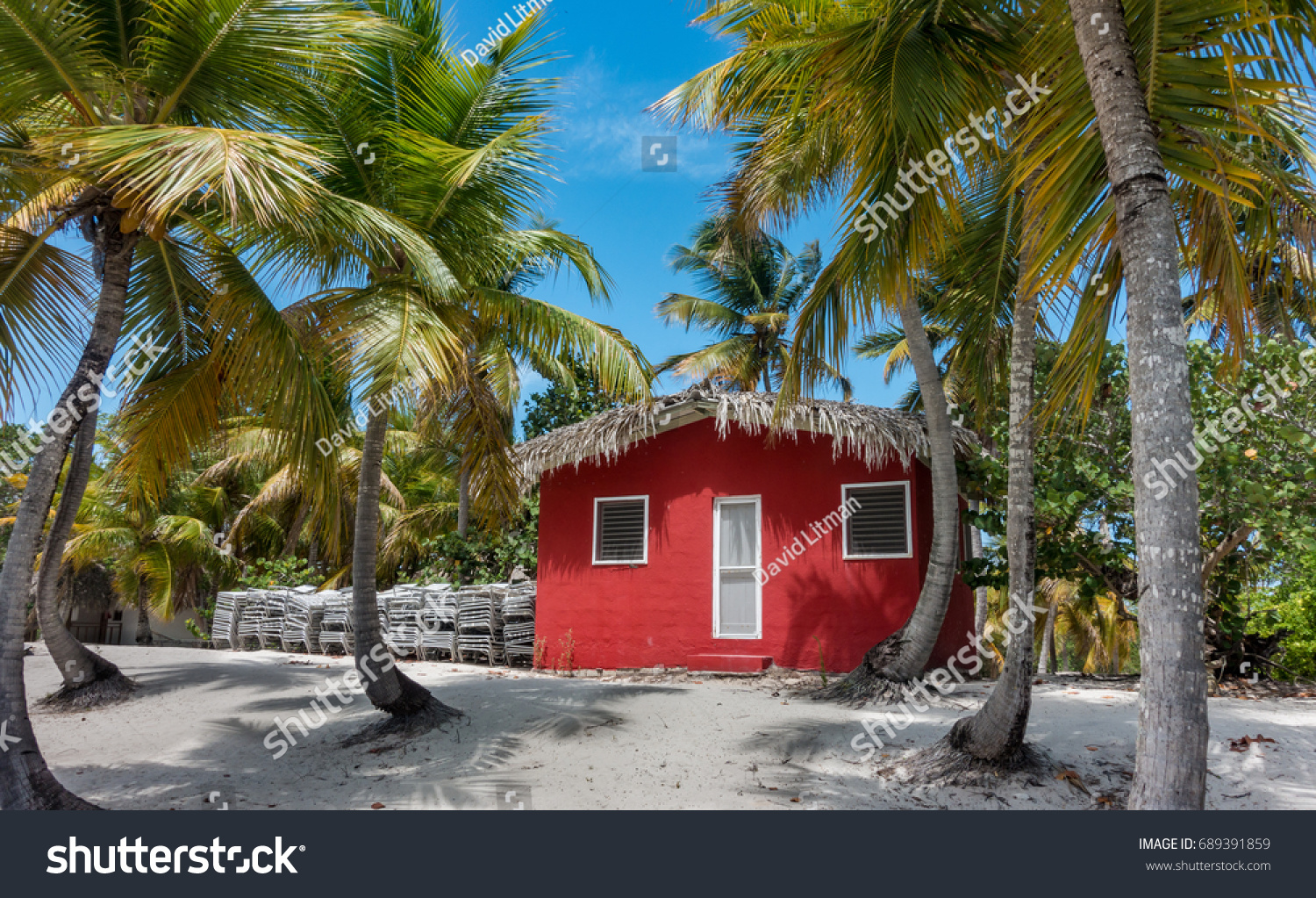A colorful red traditional beach house on the tropical Caribbean island of Catalina, in the Dominican Republic.  Visited during snorkel excursion for the all inclusive resort Club Med
