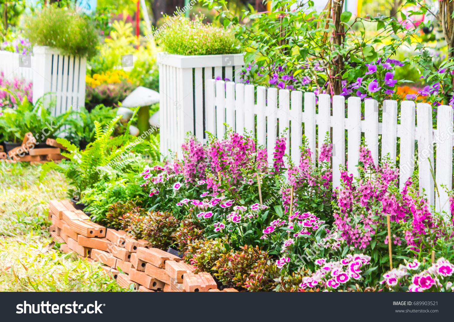 white picket fence surrounded by flowers stock photo (edit now