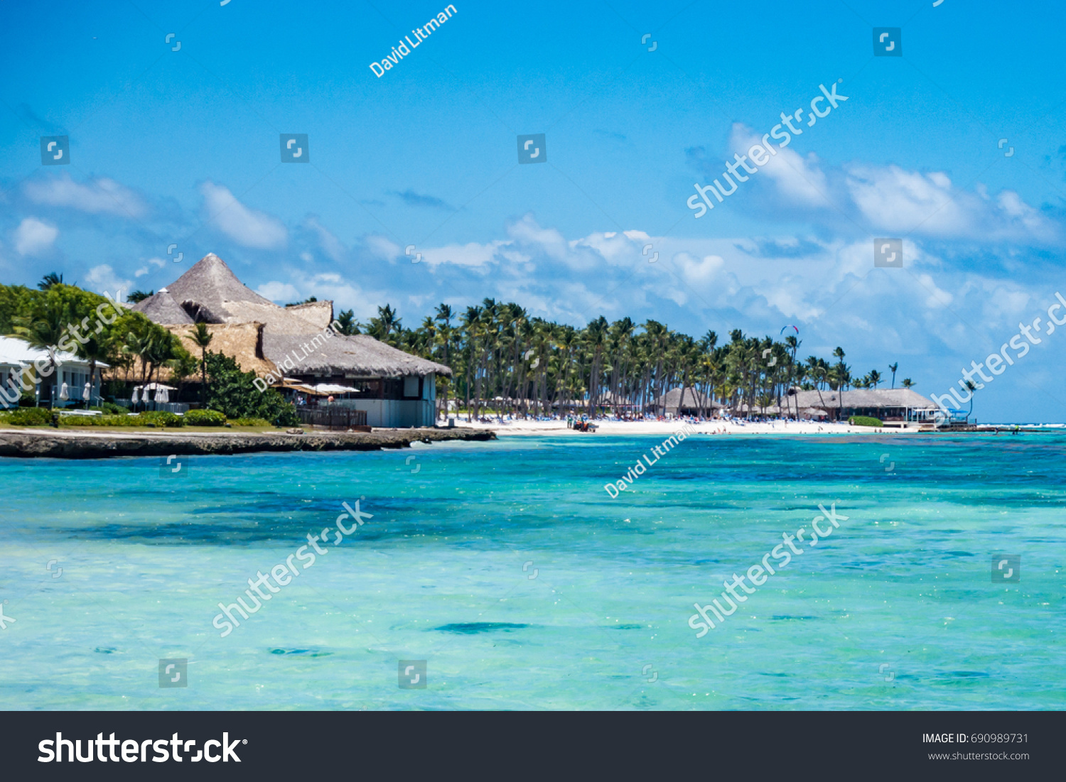 The crystal clear aqua blue Caribbean sea along the beach in Punta Cana, Dominican Republic with palm trees on a partly cloudy summer day in tropical paradise. Club Med all inclusive resort.