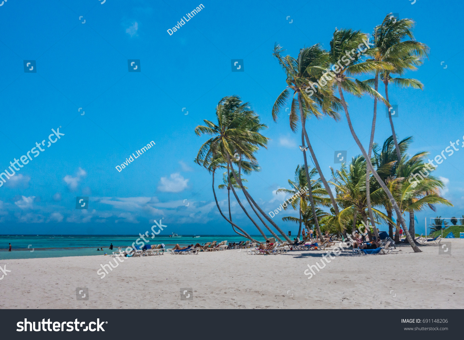 Punta Cana, Domican Repuplic - July 25, 2017: People relax on the beach on lounge chairs under the shade of palm trees on a beautiful Caribbean Island on a sunny summer day.