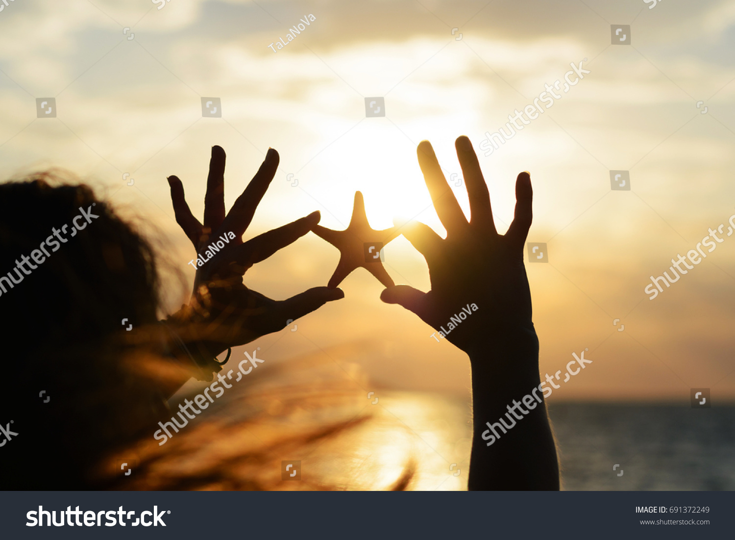 Young, beautiful with long flying hair the girl holds the starfish in her hands on the background of the sunset at the sea shore. Romantic summer sea background  #691372249