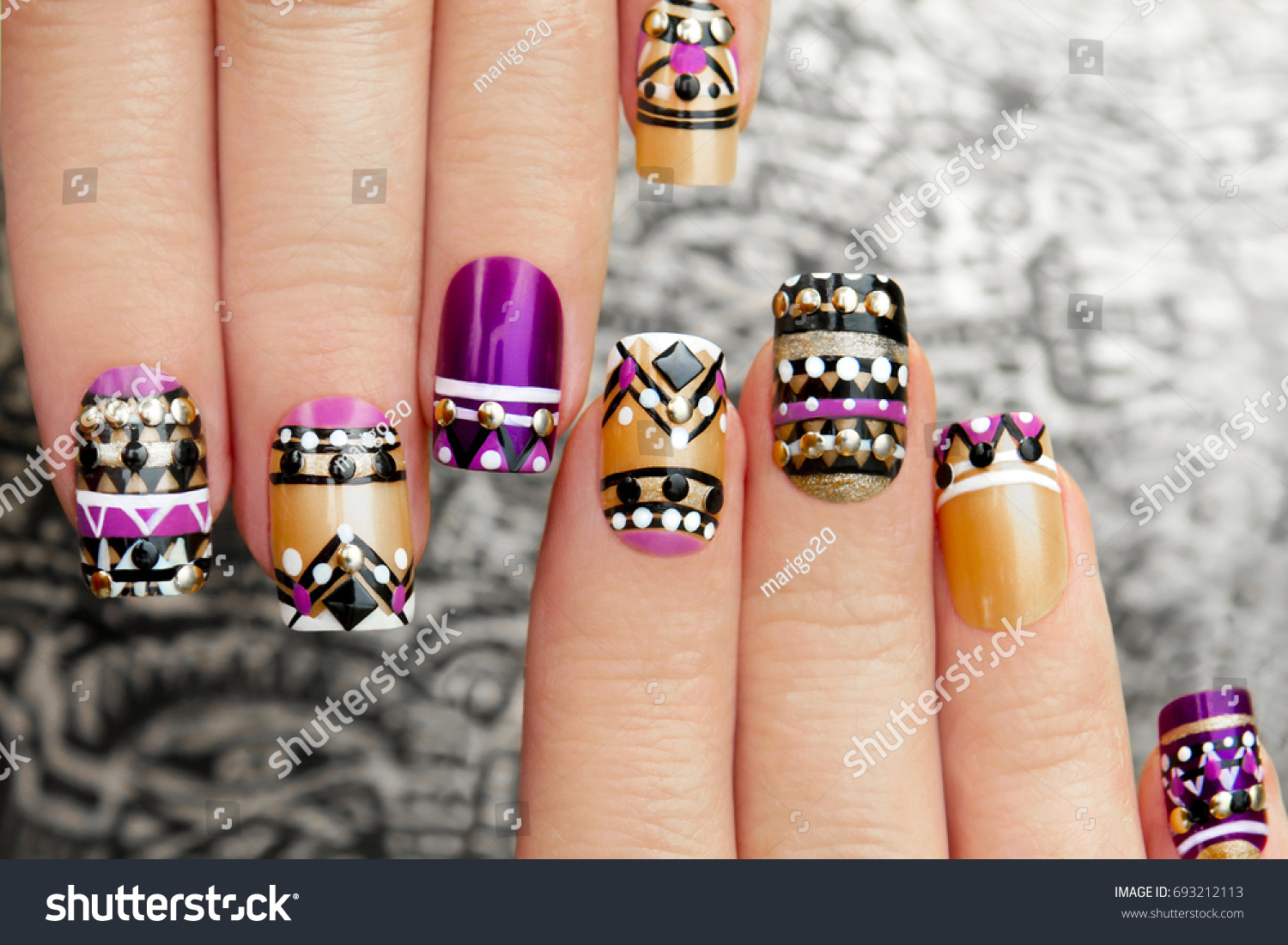 Manicure with colorful ethnic design with rhinestones on female hand close up on colorful background. #693212113