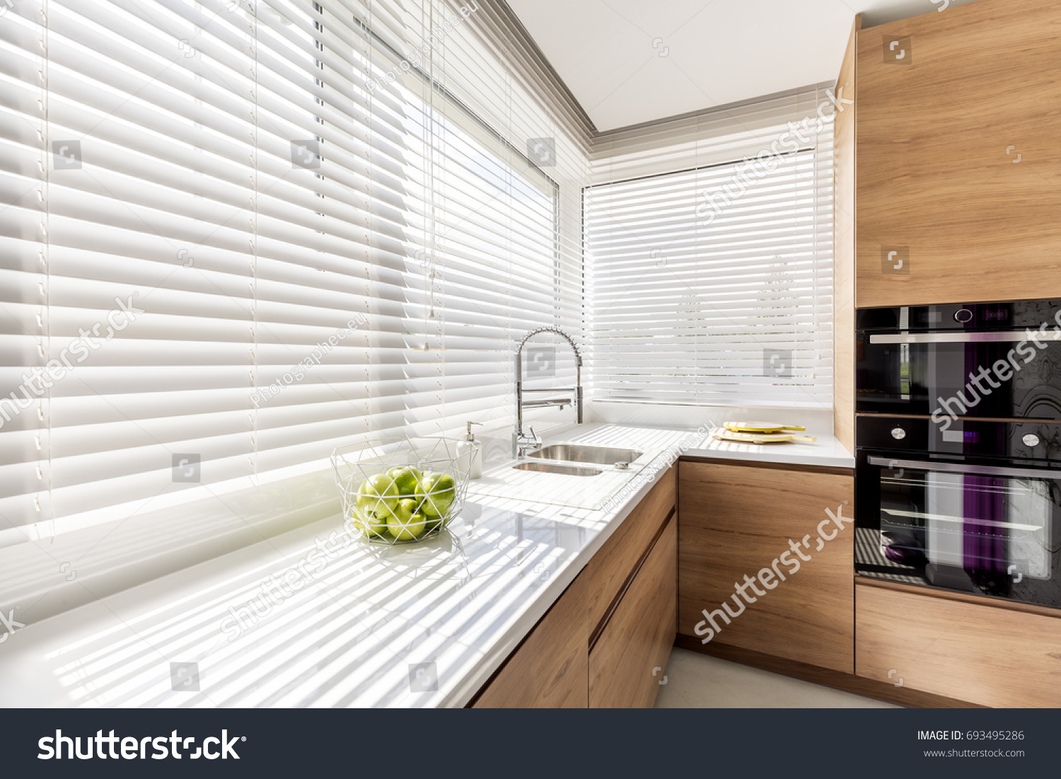 Modern bright kitchen interior with white horizontal window blinds, wooden cabinets with white countertop and household appliances #693495286