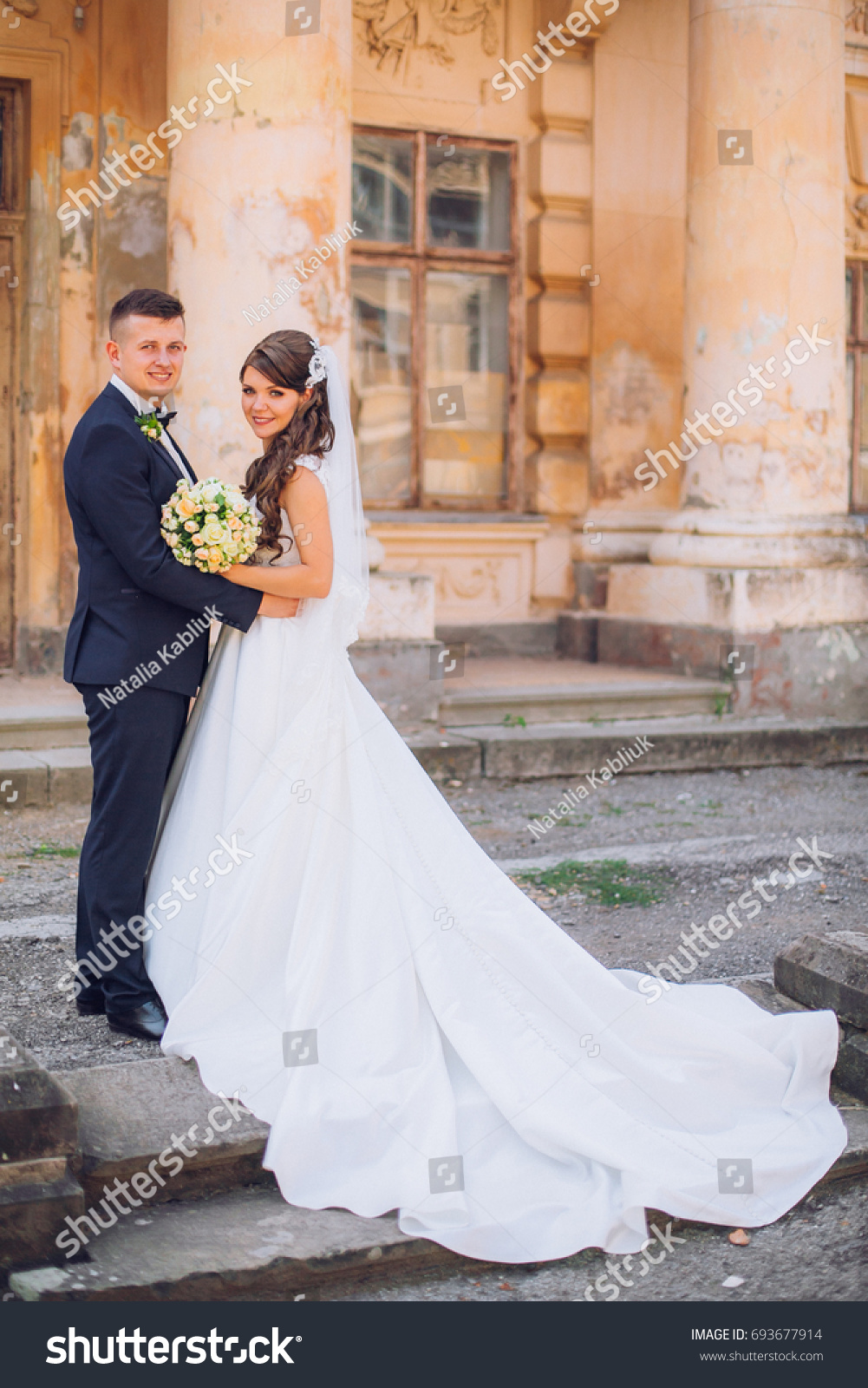 ed883516014 Beautiful romantic wedding couple of newlyweds hugging and kiss each other  near old castle with columns