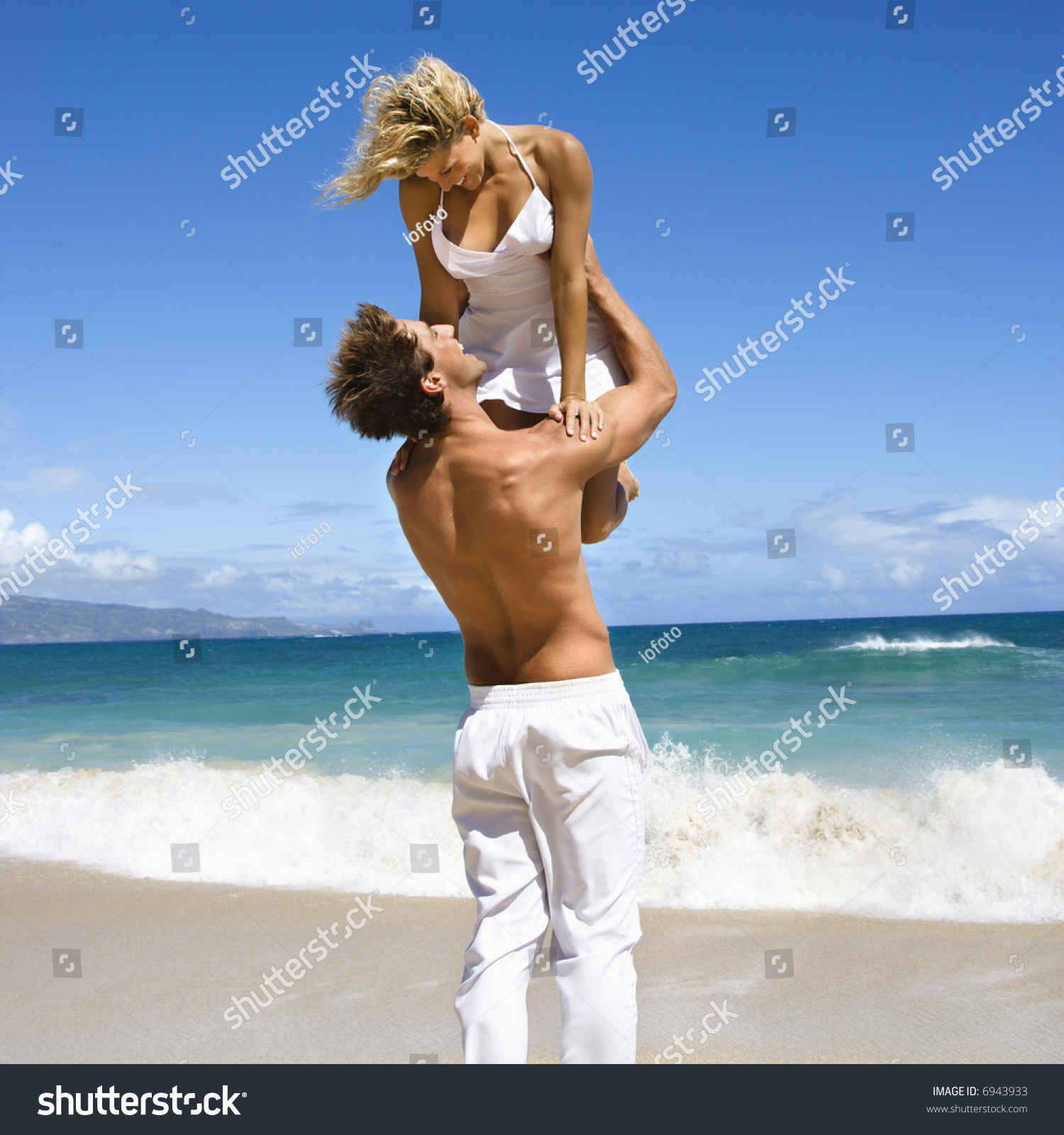 Man holding woman up in air as they look into eachother s eyes on maui