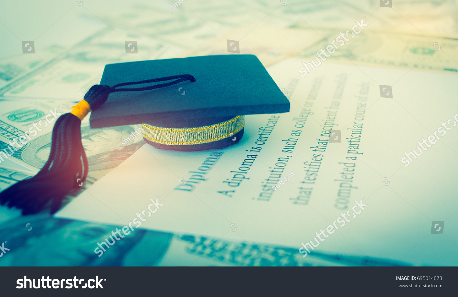 graduation cap on letter book diploma stock photo  graduation cap on a letter book diploma goals concept of graduate education abroad in