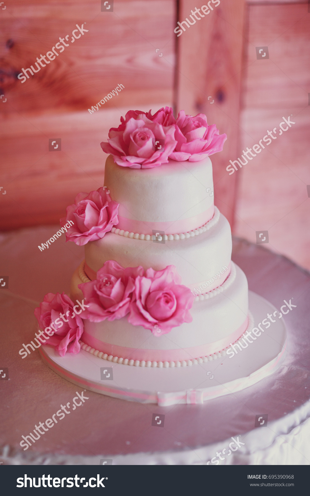 White wedding cake on wedding banquet with red rose and other ...
