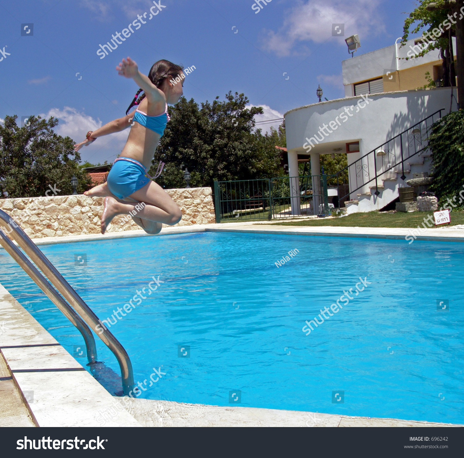 Young Girl In Blue Bathing Suit Caught Airborne While Jumping Into Swimming Pool Stock Photo