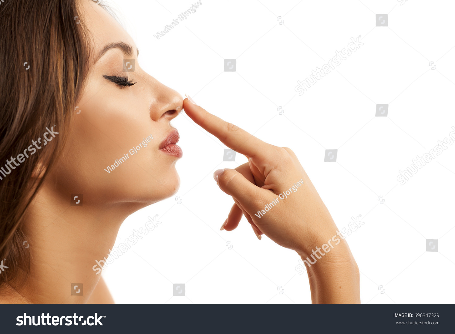 Beautiful young woman touching her nose #696347329