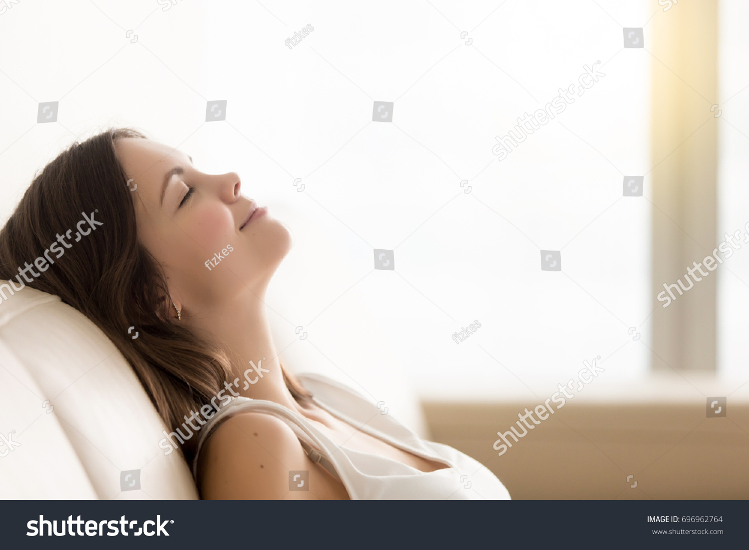 Relaxed young woman enjoying rest on comfortable sofa, calm attractive girl relaxing on couch, breathing fresh air with eyes closed, meditating at home, peace of mind, headshot portrait, copy space
