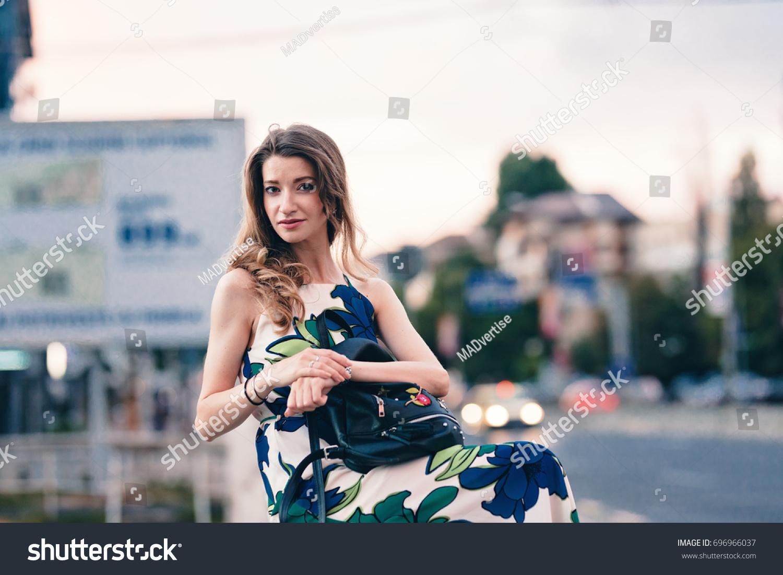 Blonde teen girl sitting on a handrail. Curled hair put forward. Looking  like something