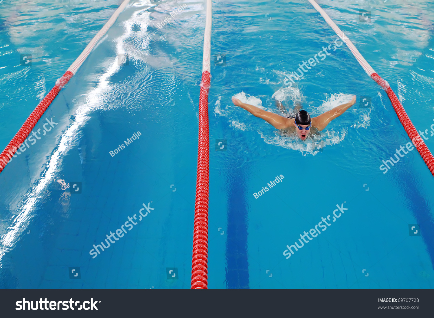 Olympic swimmer during butterfly stroke training in indoor - Olympic swimming pool opening hours ...
