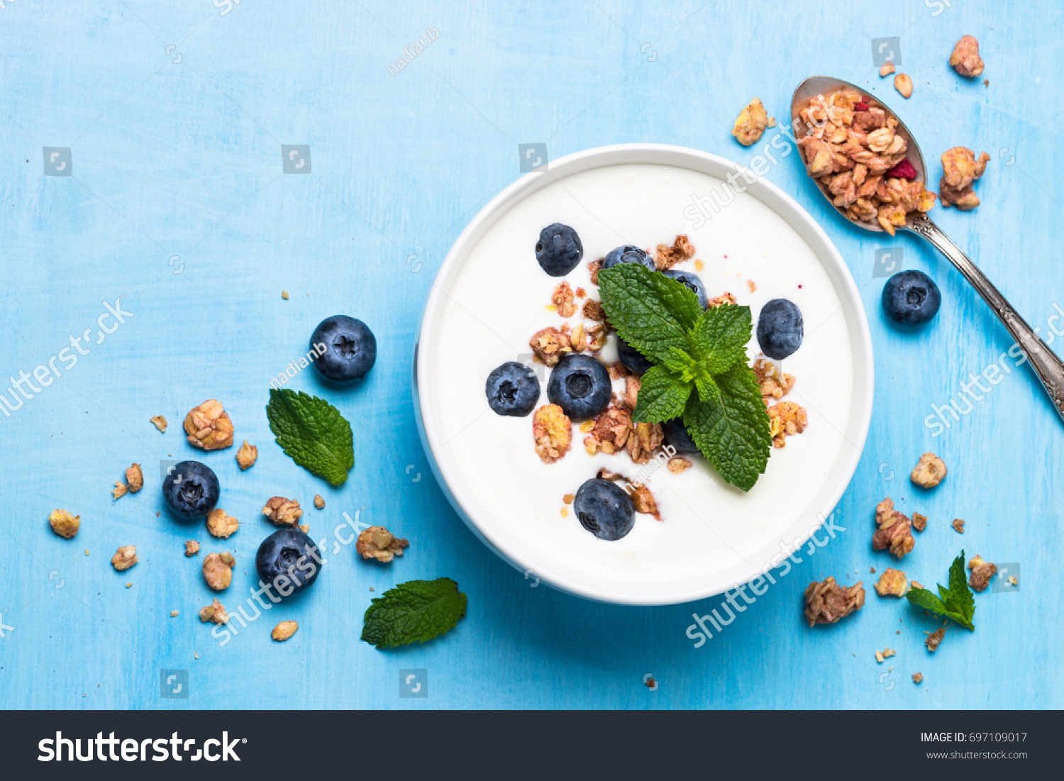 Greek yogurt granola and blueberries on blue table top view. Healthy food nutrition, snack or breakfast. #697109017
