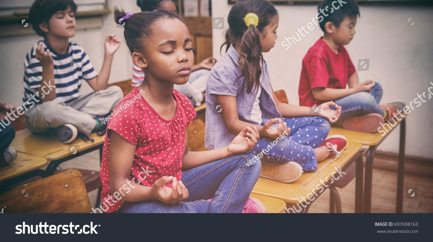 Pupils meditating in lotus position on desk in classroom at the elementary school #697698163