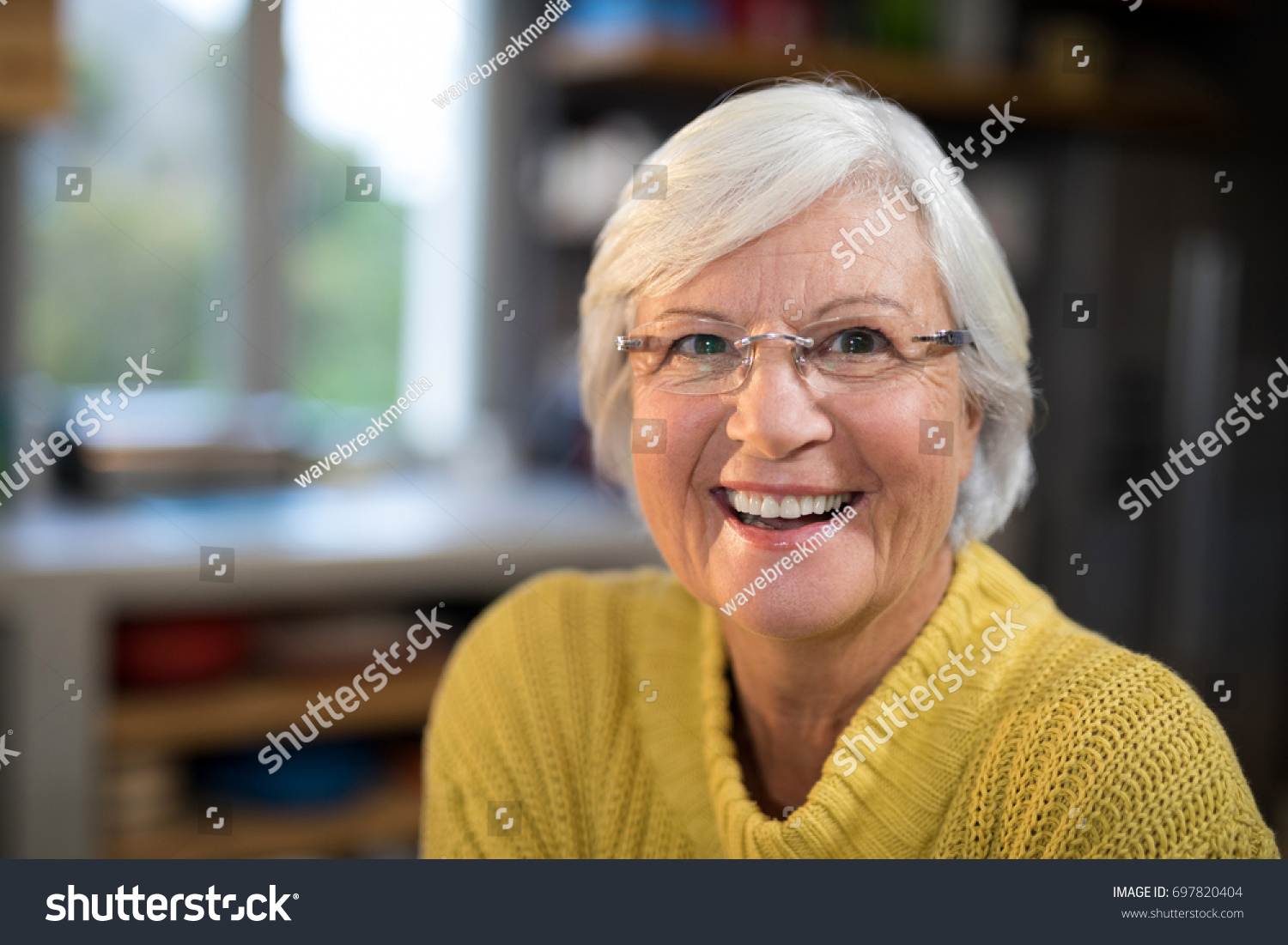 Portrait of laughing senior woman in the kitchen #697820404