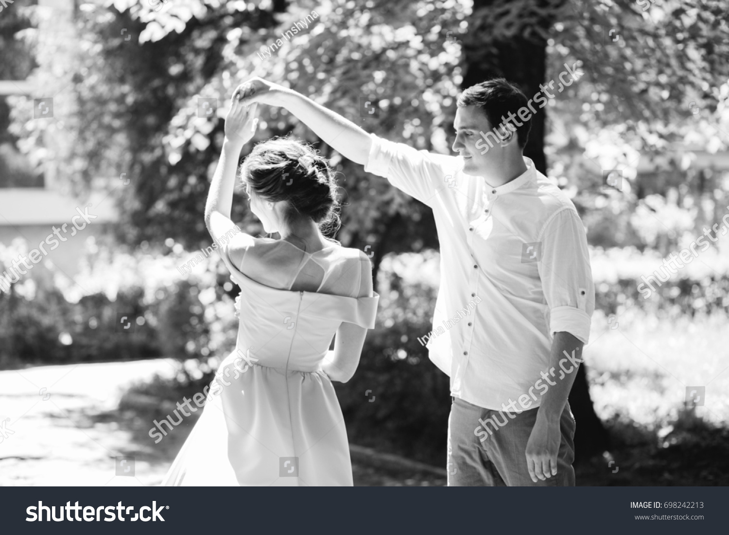 Beautiful romantic black and white photo of happy stylish newlyweds couple dancing on under blooming tree