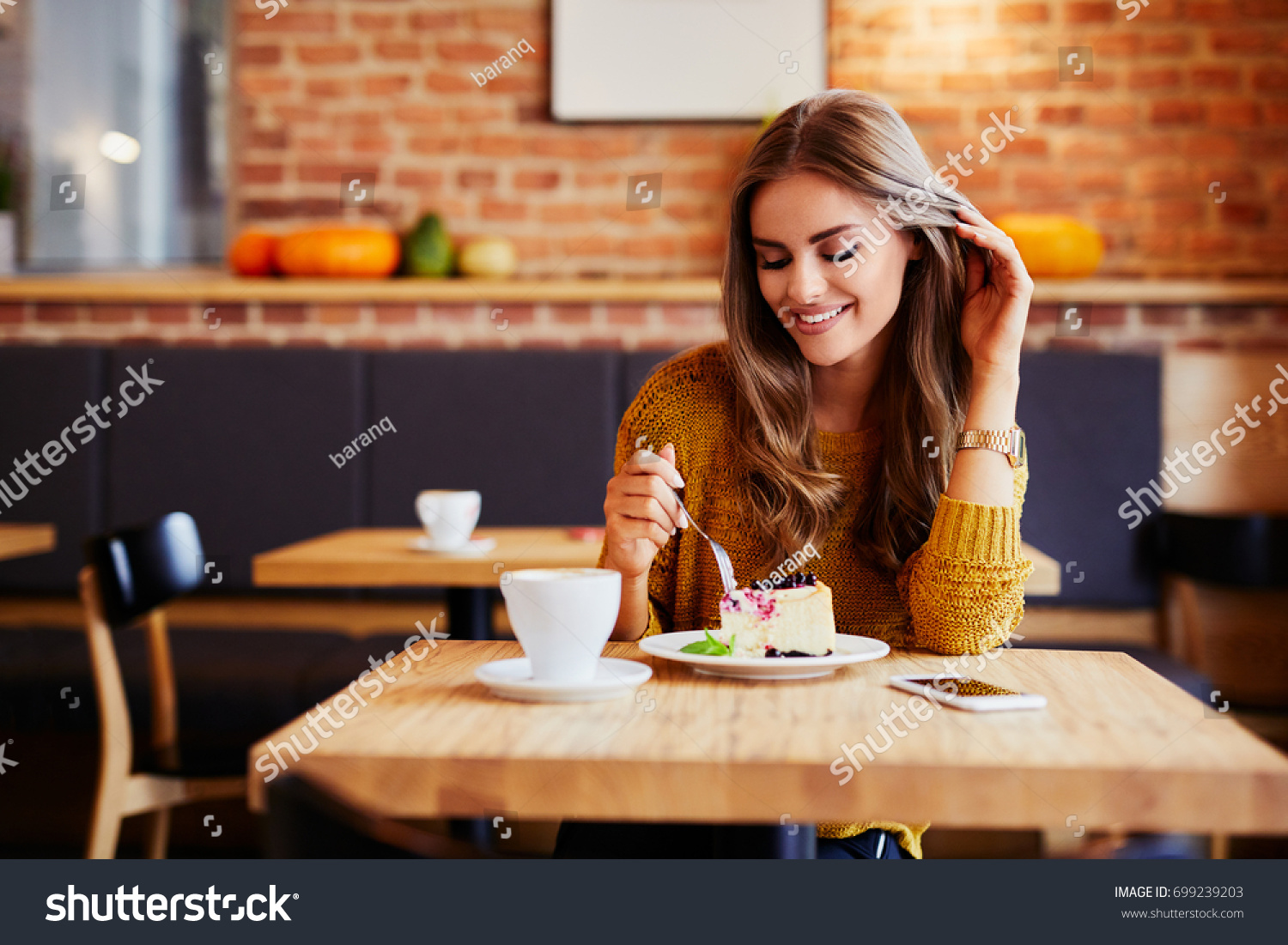 Gorgeous smiling young woman eating cake and drinking coffee at a cafeteria #699239203
