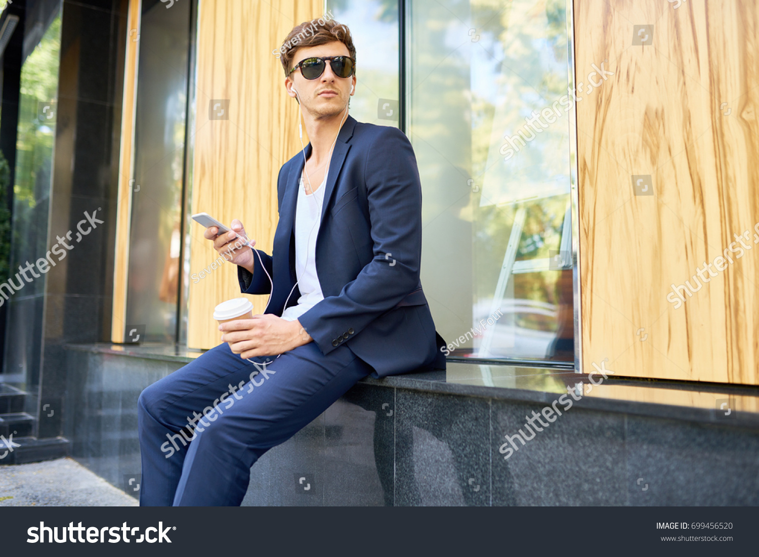 Portrait Of Handsome Young Man Posing Using Smartphone Outdoors Enjoying Coffee Break
