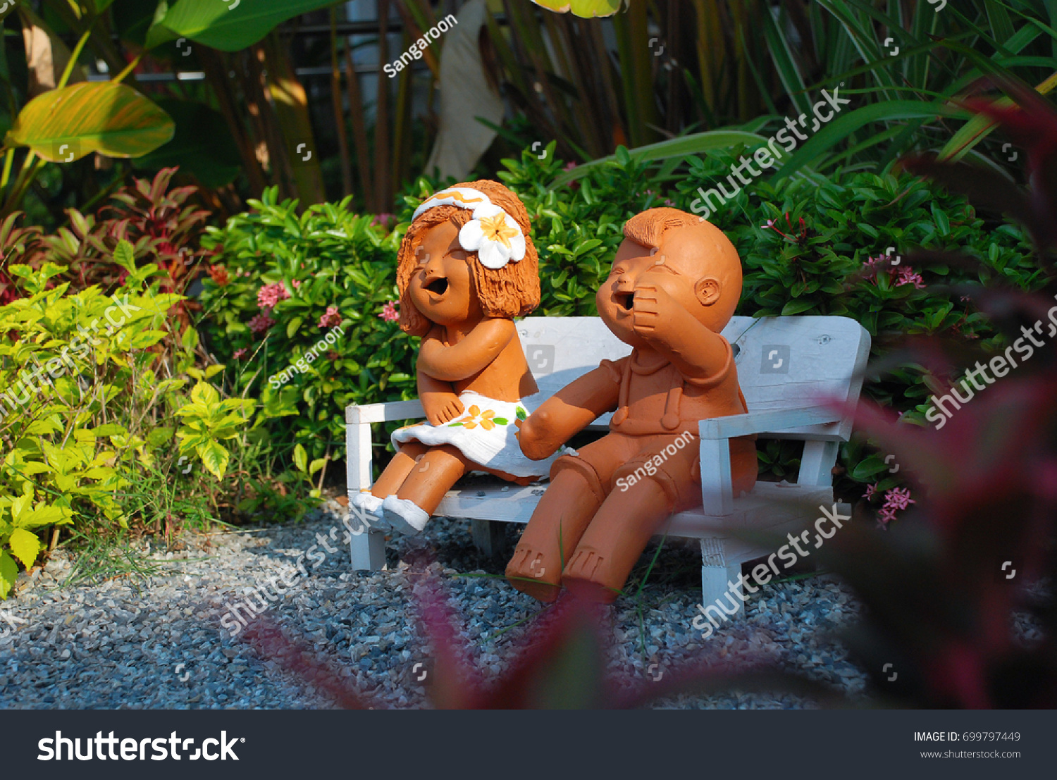 Smiling And Laughing Clay Doll In The Garden