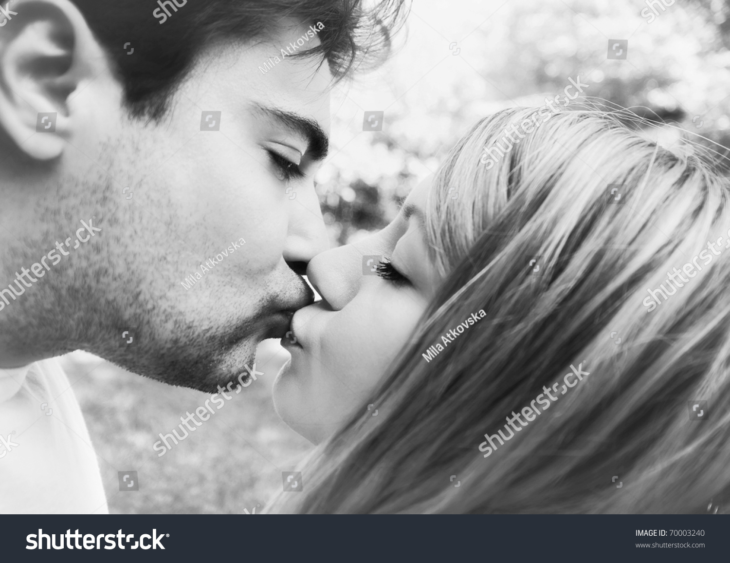 Black white closeup of a young couple kissing