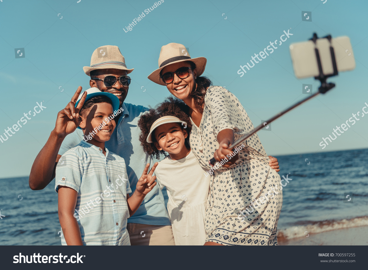 happy african american family taking selfie with smartphone on beach #700597255