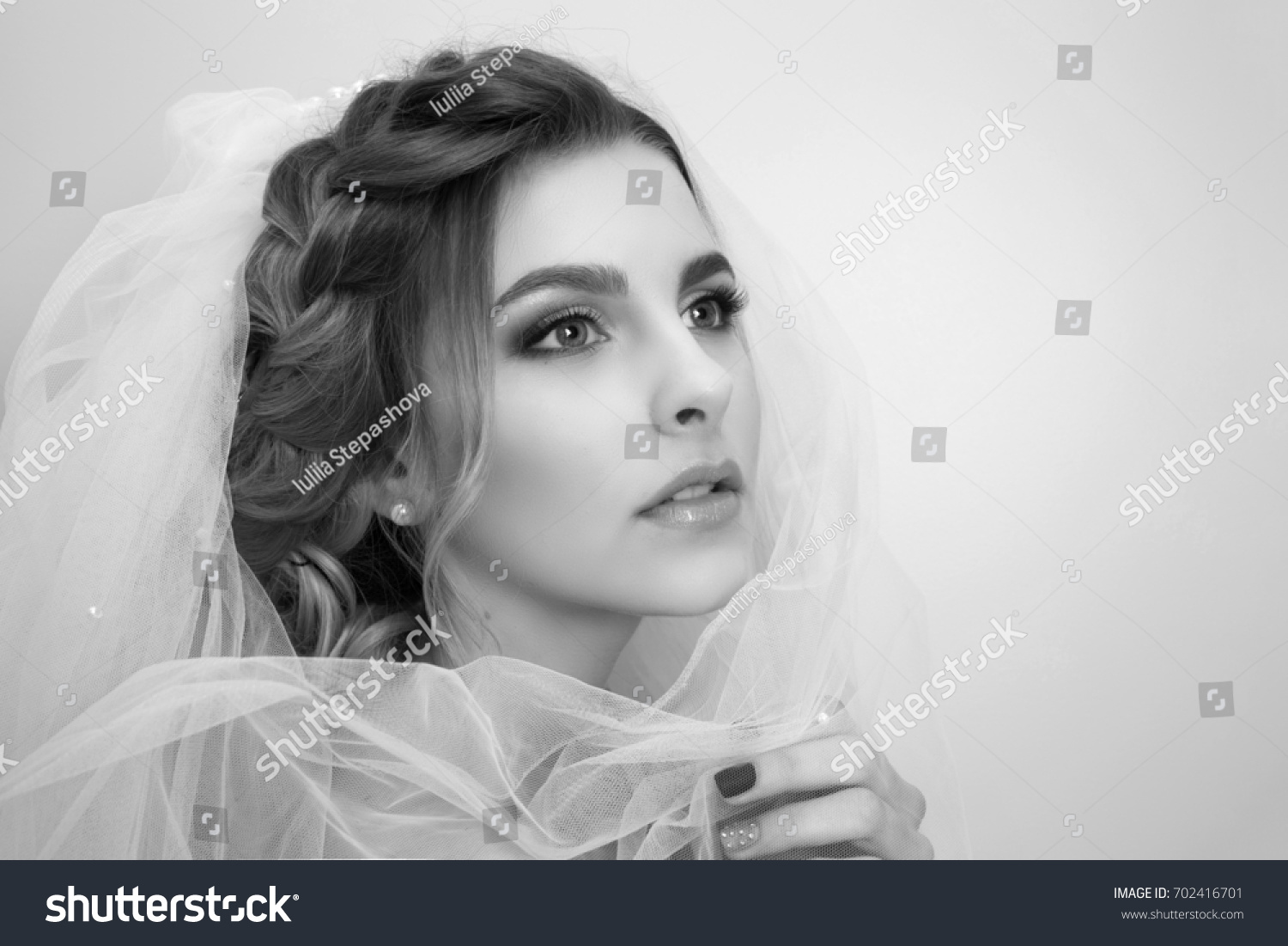 Beautiful young woman bride with wedding hairstyle portrait on a light background in pastel colors