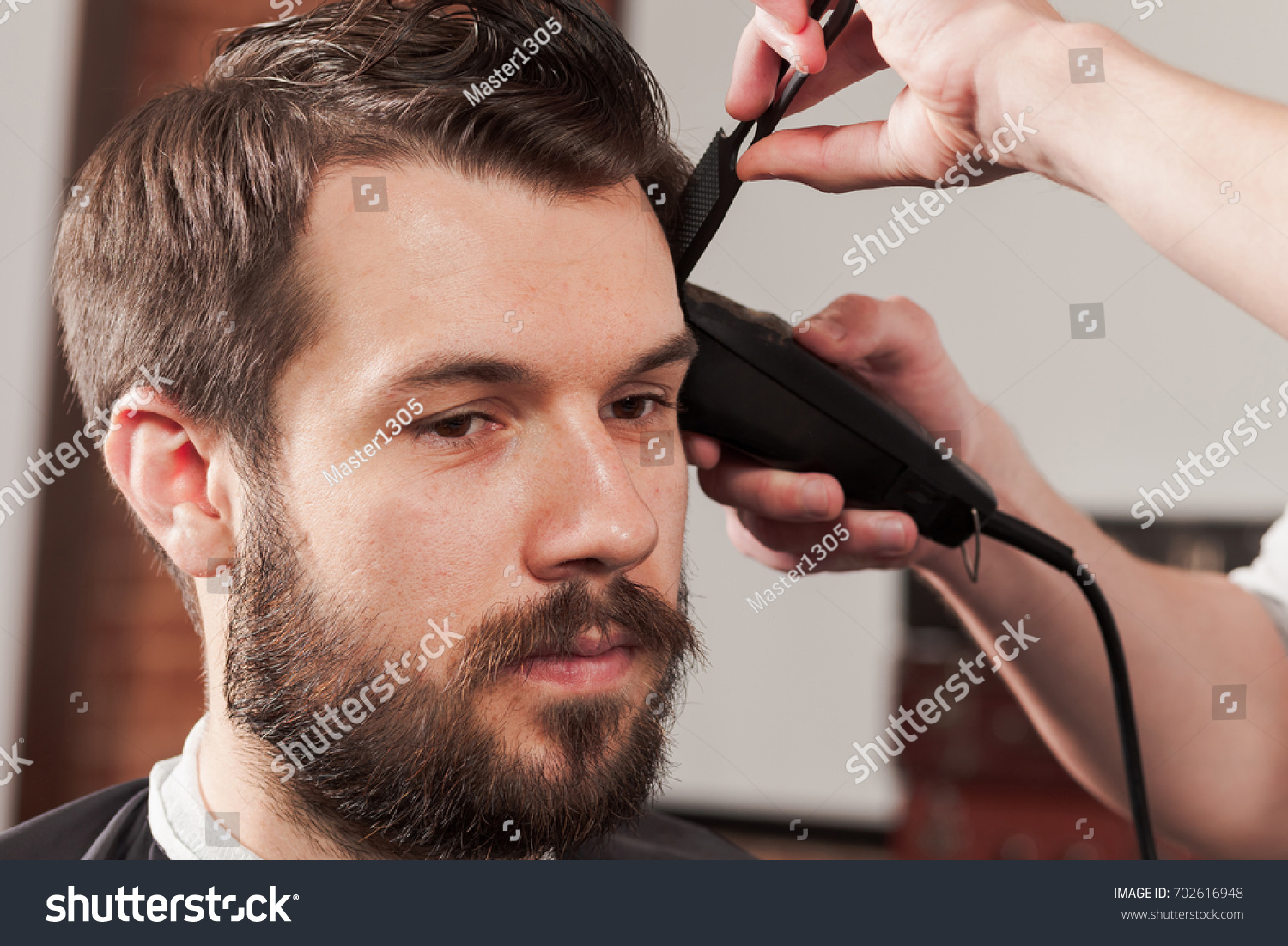The Hands Of Barber Making Haircut To Young Man In Barbershop Ez