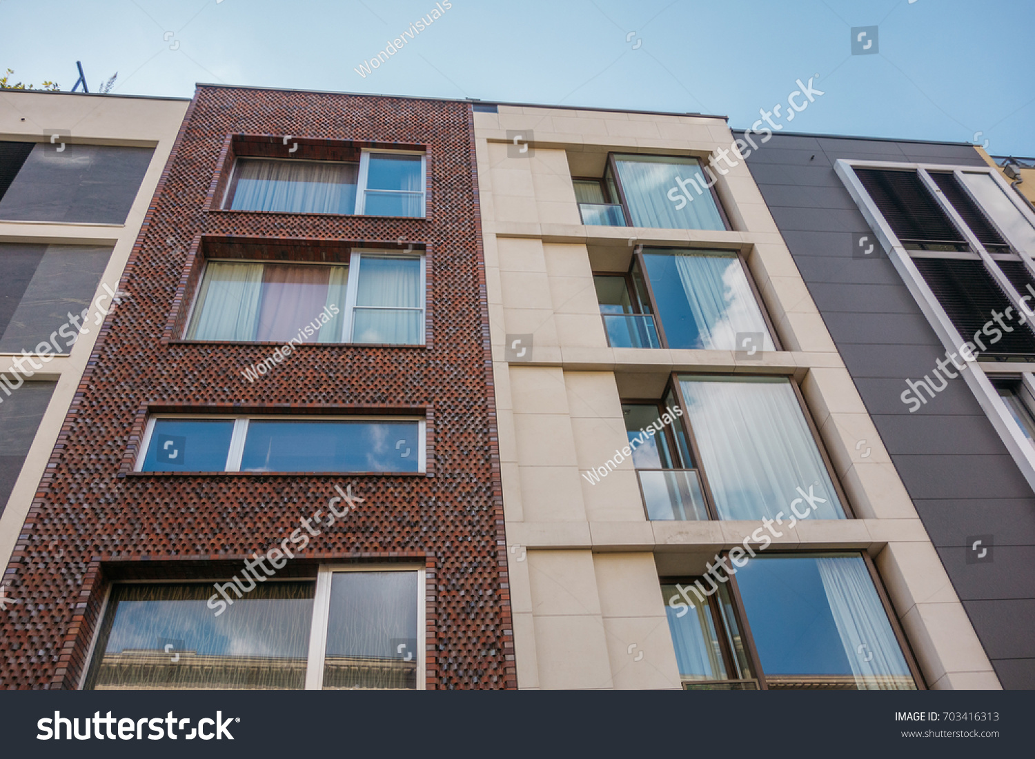 big glass windows small id 703416313 brown brick facade next to white and grey townhouse building with