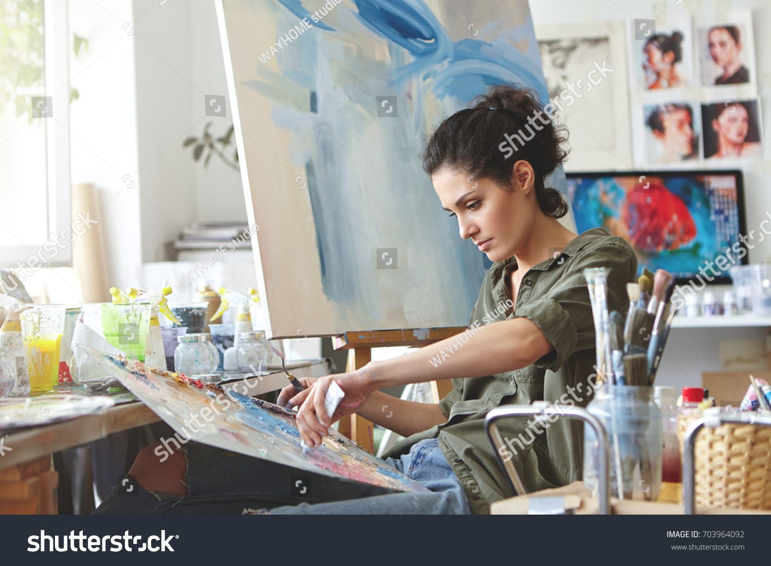 Young female student having classes at art studio, learning how to draw landscapes, trying to mix different watercolors on cardboard. Concentrated woman with dark hair, dressed casually, painting #703964092