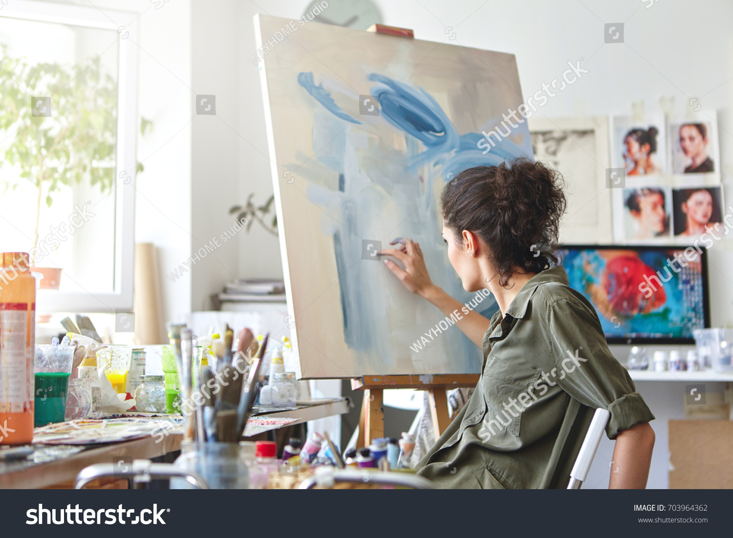 Art, creativity, hobby, job and creative occupation concept. Rear view of busy female artist sitting on chair in front of easel, painting with fingers, using white and blue oil or acrylic paint #703964362