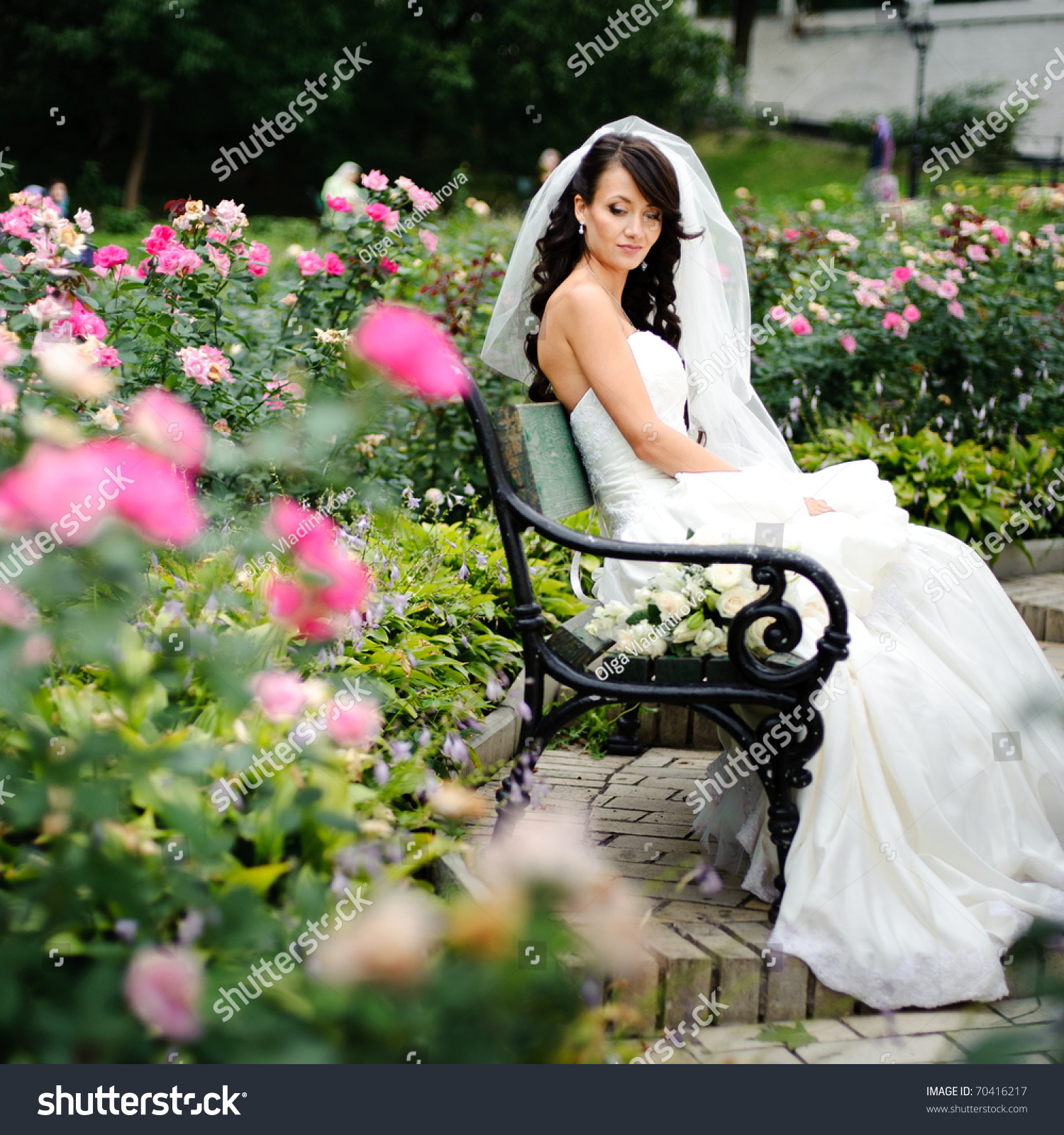 Beautiful girl in a wedding dress sitting alone among the roses